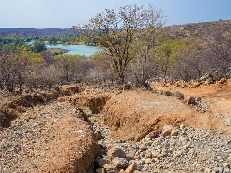 Rough offroad track with large ruts along Kunene River between Kunene River Lodge and Epupa Falls, Namibia, Africa. Very rough offroad track with large rocks and stock images