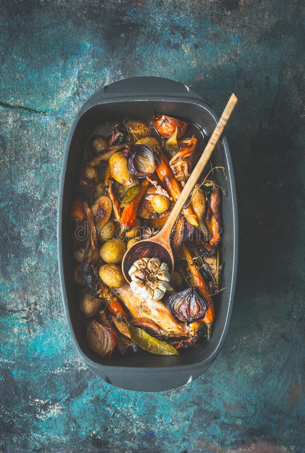Very rustic roasted vegetables stew or ragout with wild game and wild fowl and forest mushrooms in black backing dish with wooden stock photography