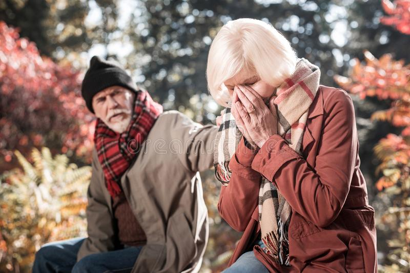 Depressed crying aged woman covering her face royalty free stock photography