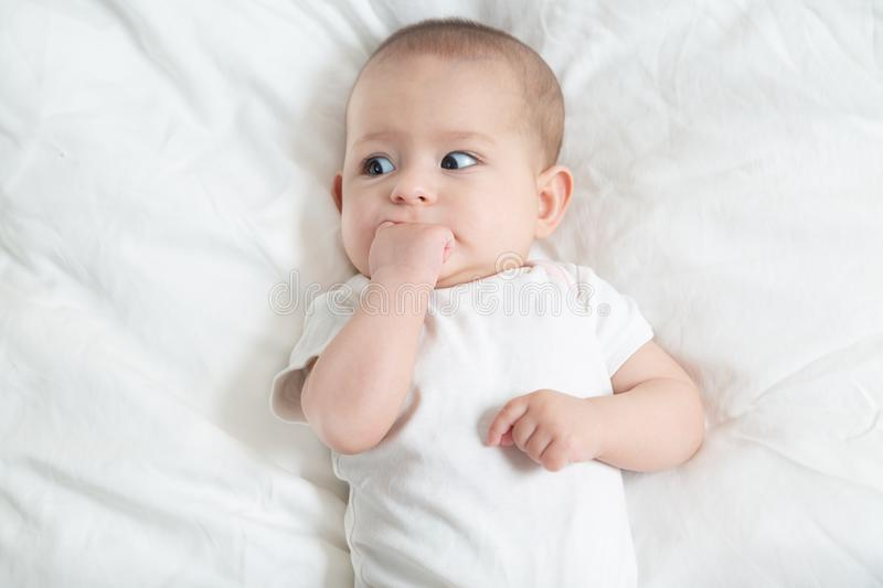 Very scared little baby girl in white lying on a white bed. The baby teething stock image
