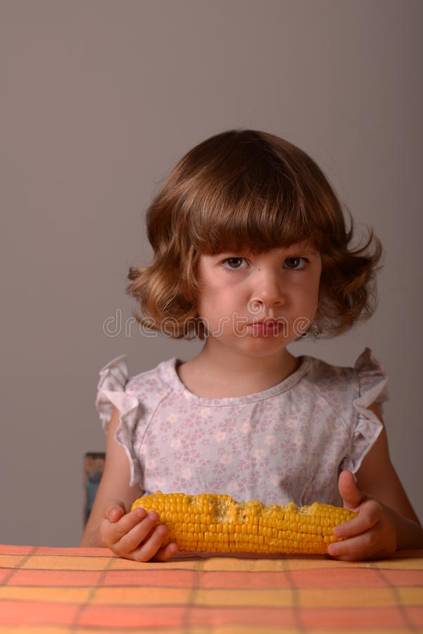 Very serious girl with maize royalty free stock image