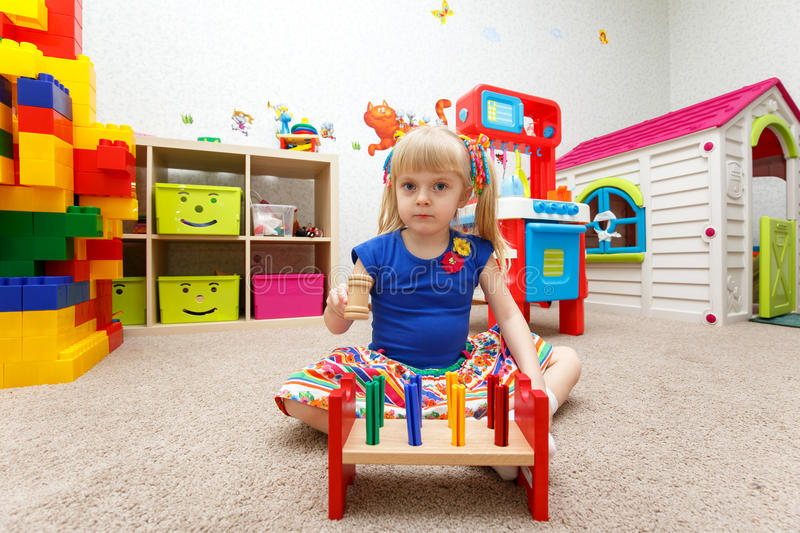 Very serious little girl playing with wooden hammer in kindergarten stock photos