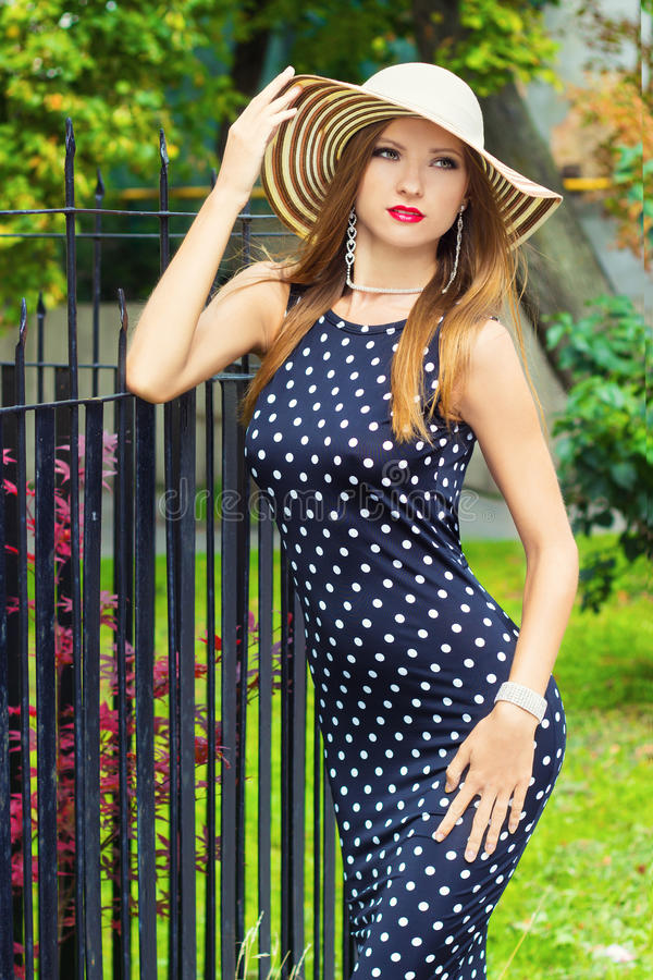 Very girl with red lips in the hat dress with polka dots standing around outside in the Park on a Sunny summer day royalty free stock photography