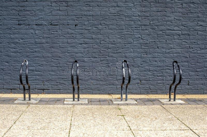 Very simple bike, bicycle racks, painted black in front of a black brick wall. Very simple bike, bicycle racks, painted black in front of a black brick wall royalty free stock photo