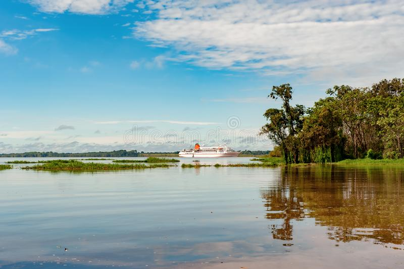 Cruiser, Cruise Liner on River Amazon with typical riparian vegetation on shore. Very small cruise liner expedition ship on the Amazon in beautiful landscape stock photo