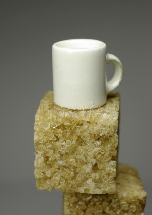 Very small cup on piece of sugar royalty free stock photo