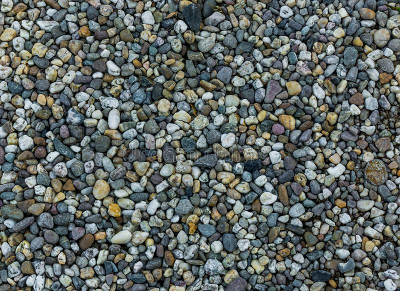 Very small and tiny pebble stone rocks in macro close up in diverse colors garden ground decoration background stock image
