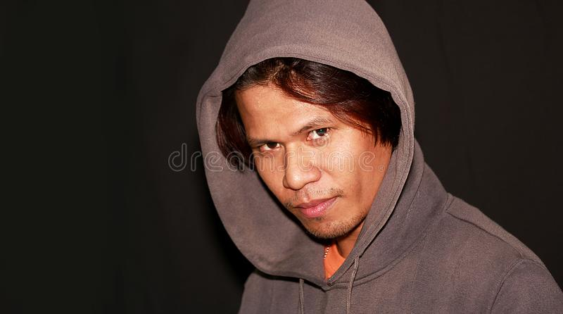 Very strong look of an asian man- portraiture enhance lighting. With copy space stock photos