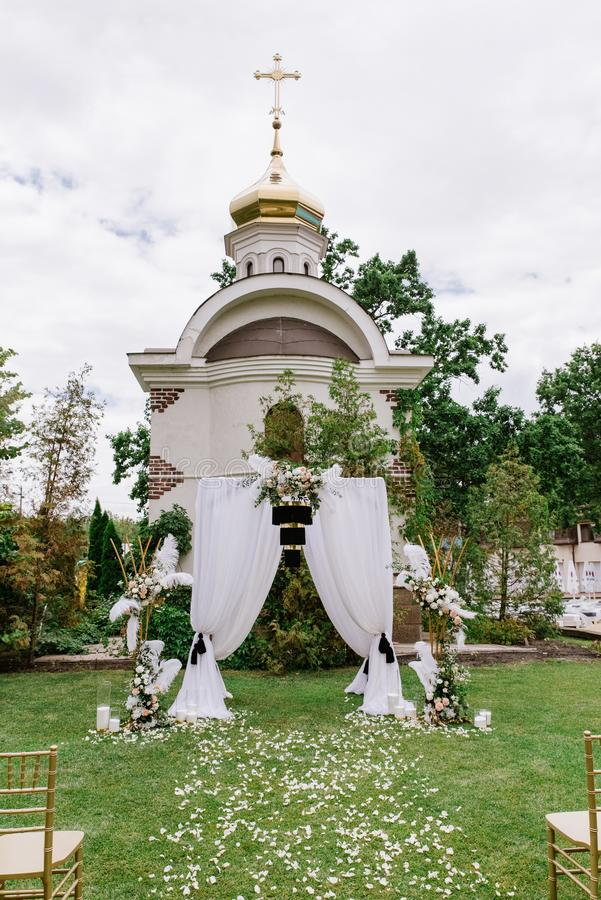 A very stylish white wedding arch with unusual black decoration. Place for wedding ceremony. Against the background of the temple stock photography