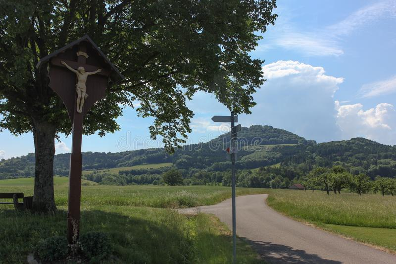 Countryside with crucifix. On a very sunny day in june in south germany you see summer landscape with road and crucifix and shields for ways and blue sky on the stock photos
