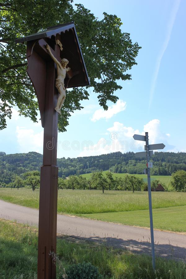 Countryside with crucifix. On a very sunny day in june in south germany you see summer landscape with road and crucifix and shields for ways and blue sky on the stock photo