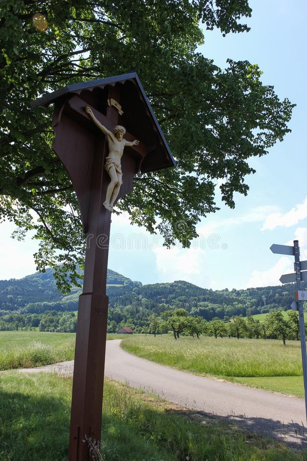 Countryside with crucifix. On a very sunny day in june in south germany you see summer landscape with road and crucifix and shields for ways and blue sky on the royalty free stock photography