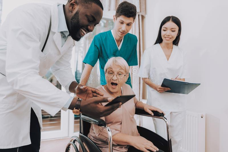 Very Surprised Patient. Doctor Show Test Results. Elderly Woman Looks in Hospital Case. Doctor with Tablet. Patient on Wheelchair. Nursing Home. Doctor in stock images