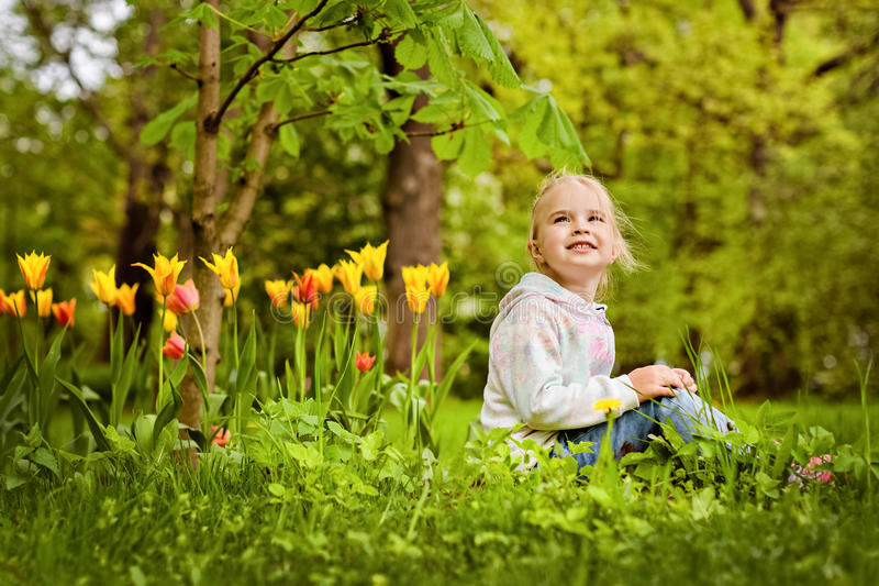 Very sweet beautiful blonde girl sits near the flower bed of red stock photos