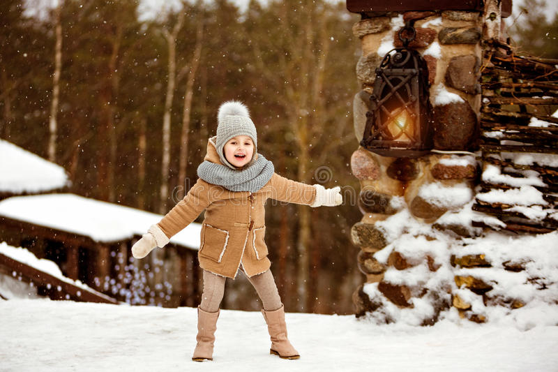 Very sweet beautiful little girl child in the beige coat is happ stock photography