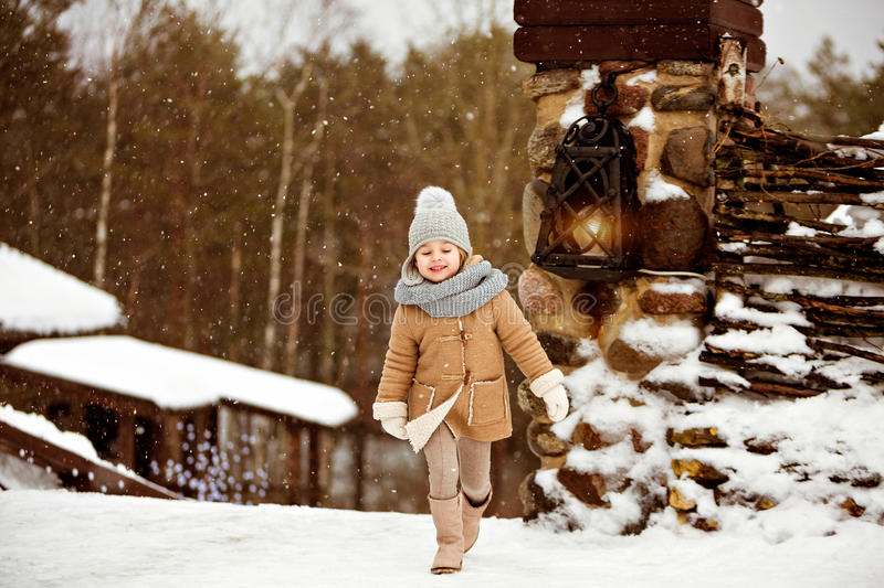 Very sweet beautiful little girl child in a beige coat smiles an stock photography