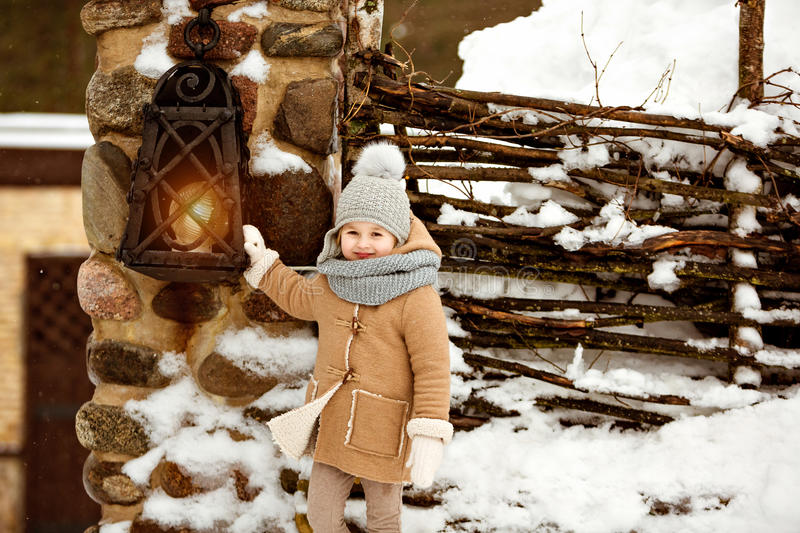 Very sweet beautiful little girl child in a beige coat smiling a. Gainst winter village near the lantern royalty free stock images