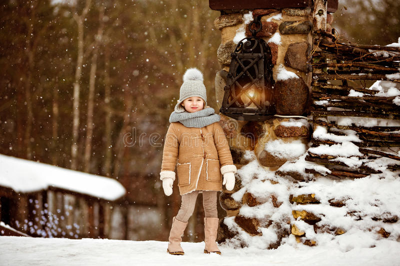 Very sweet beautiful little girl child in a beige coat stands an royalty free stock images