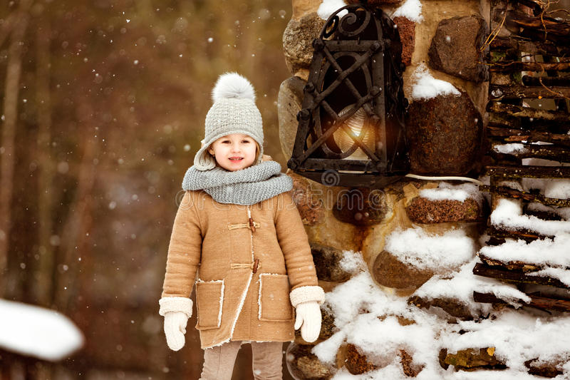 Very sweet beautiful little girl child in the beige coat is on t stock image