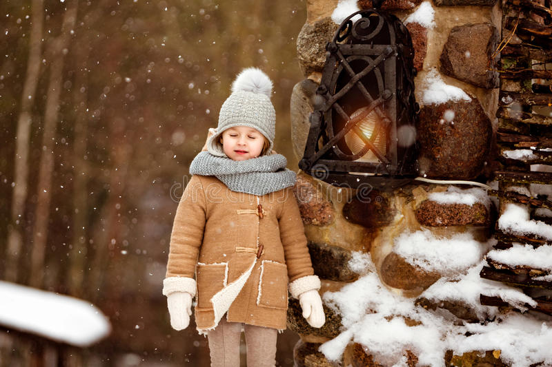 Very sweet beautiful little girl child in a beige coat turned a royalty free stock photo
