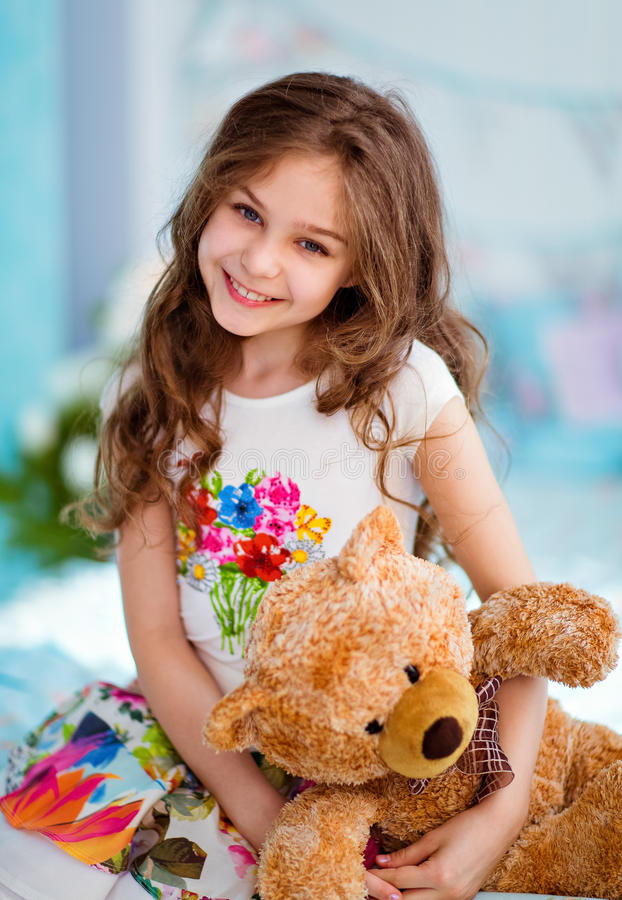 Very sweet smiling curly haired young girl sitting on the bed wi royalty free stock image
