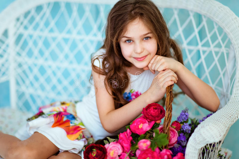Very sweet smiling curly haired young girl sitting near the bask stock image