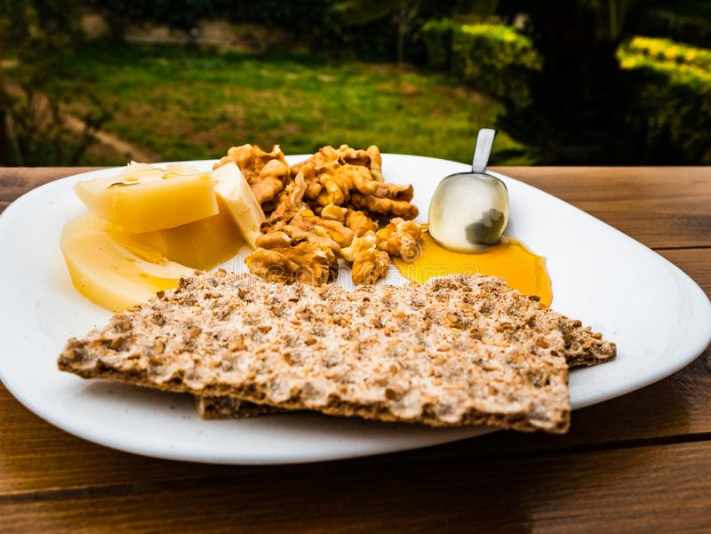 Very tasty italian healthy rustic sweet and salty breakfast with homemade cow`s milk cheese, walnuts, honey stock photos