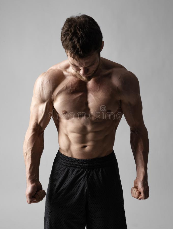 A very tense man with a naked torso in black shorts looks down on a gray background royalty free stock photo