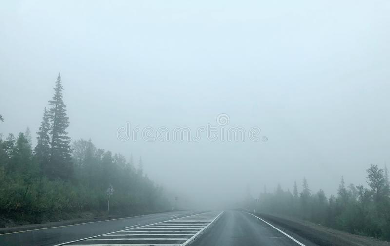 Very thick fog. The road disappearing into the fog. The concept of danger on the road.  stock photos