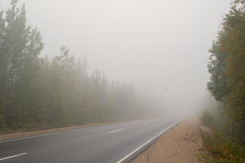 Very thick fog. The road disappearing into the fog. The concept of danger on the road.  royalty free stock photos