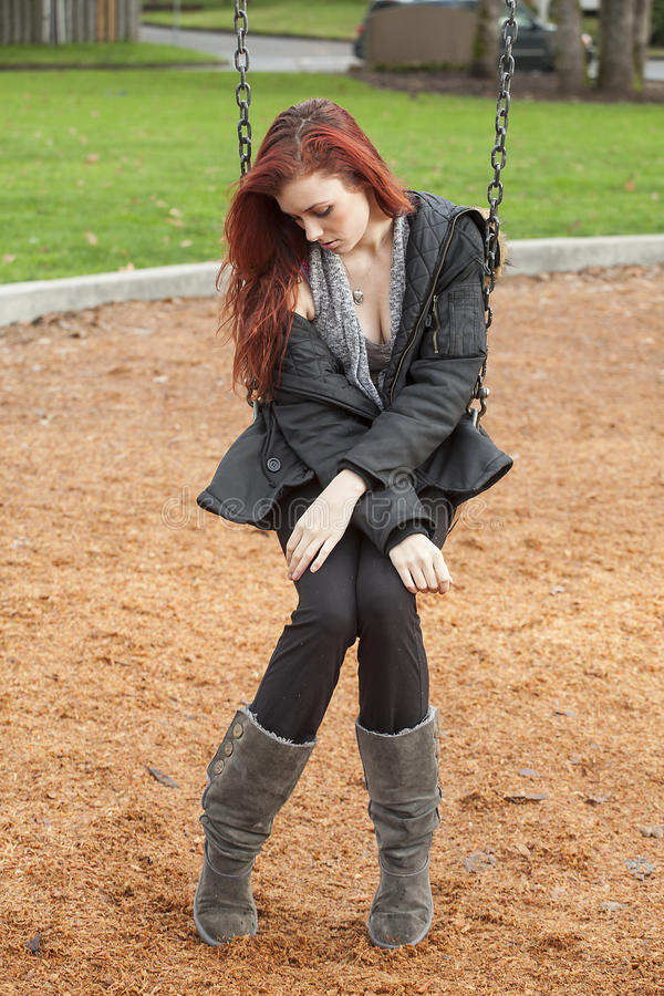 Very Unhappy Young Woman with Beautiful Auburn Hair on a Swing stock photos