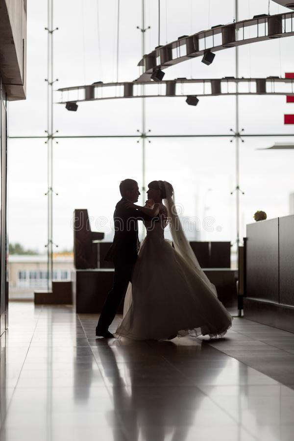 Verzacht dans van mooie jonggehuwden in een grote zaal stock foto