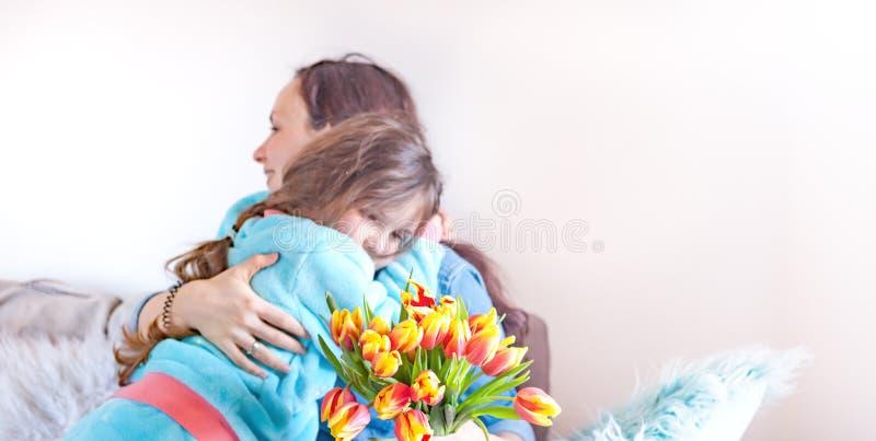 Verzacht omhelzingenmoeders en dochters, gelukwensen op de vakantie en bloemen Het concept van de de groetkaart van de moeder` s  royalty-vrije stock afbeeldingen
