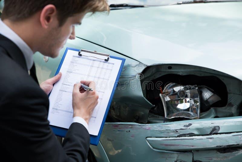 Verzekeringsagent die auto na ongeval onderzoeken royalty-vrije stock afbeeldingen