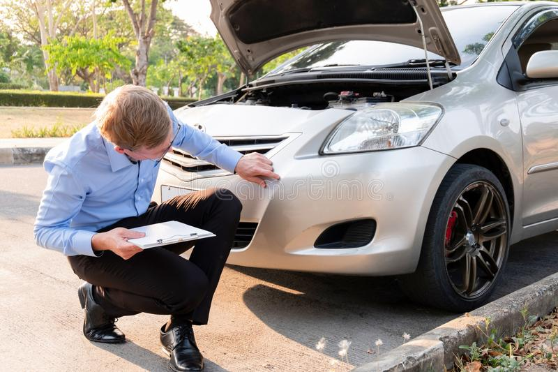 Verzekeringsagent het schrijven document op klembord die auto na ongeval, Verzekeringsconcept onderzoeken stock foto's