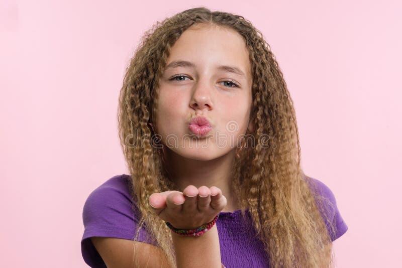 Verzendt de portret aantrekkelijke positieve tiener luchtkus over roze achtergrond royalty-vrije stock afbeelding