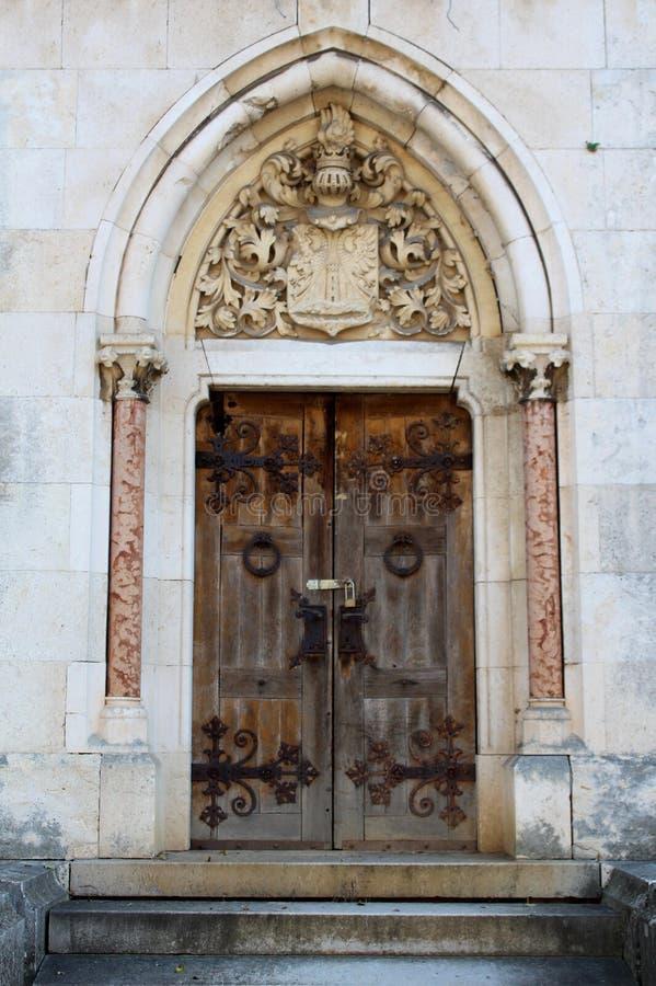 Verzierte in hohem Grade geschnitzten Steineingang zum Familiengrab mit den großen starken Holztüren, die mit Metallvorhängeschlo stockfotografie