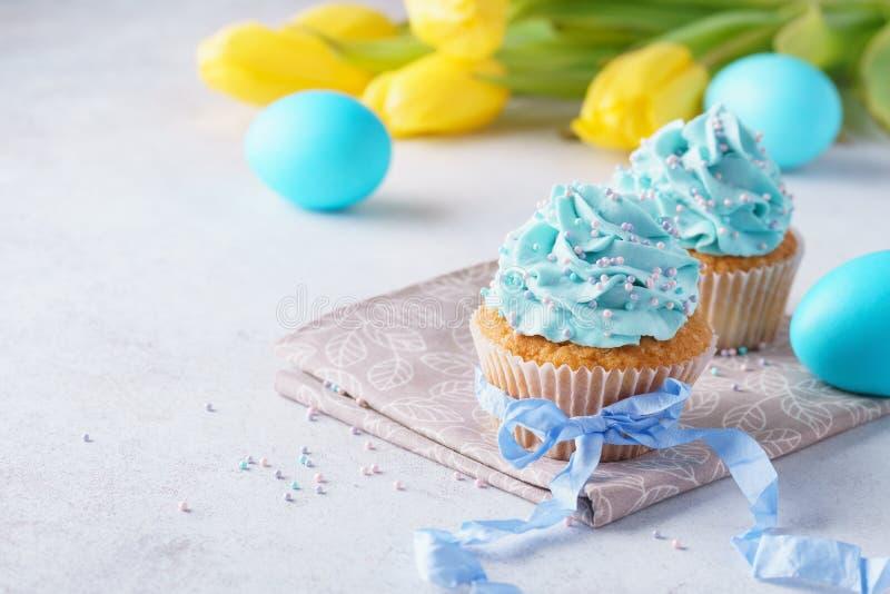 Verzierte kleine Kuchen mit Sahne, blaue Eier und Tulpen für Ostern lizenzfreies stockbild