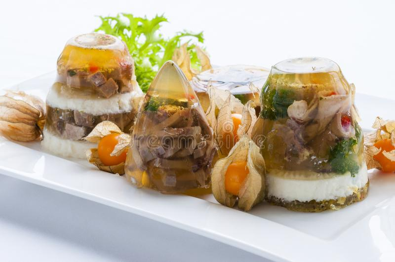 Verzierte Nahrung Kalter Teller des Aspiks mit Fleisch, Gelee, Gemüse, Grün stockbild