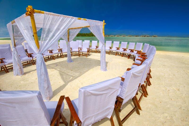Verzierte Stühle und Bogen für Hochzeitszeremonie auf Tropeninsel mit sandigem Strand und tourquise klarem Wasser lizenzfreie stockfotos