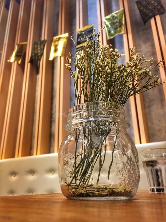 Verzierte trockene Blumen im Glasgefäß stockfotos