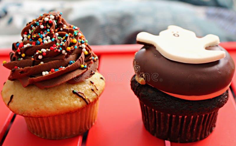 2 verzierten Muffins auf einer roten Oberfläche stockfotos
