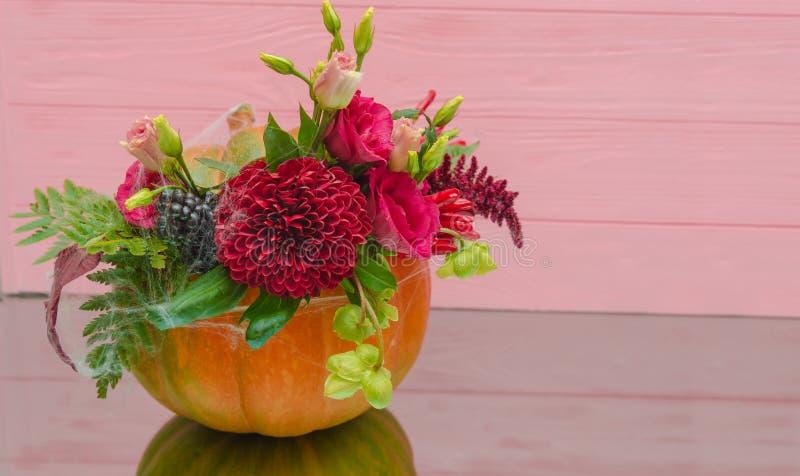 Verzierter Halloween-Kürbis mit Blumen und Blättern auf rosa Holz stockfotografie