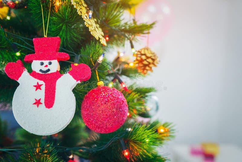Verzierter Weihnachtsbaum mit dem Hängen des roten Balls, Schneepuppe lizenzfreie stockbilder