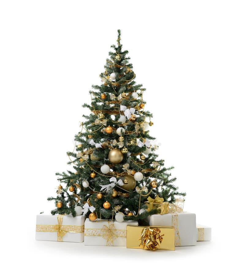 Verzierter Weihnachtsbaum mit künstlichen Goldkugeln der goldenen Patchworkverzierung und großem Geschenk stellt sich für neues J stockbild