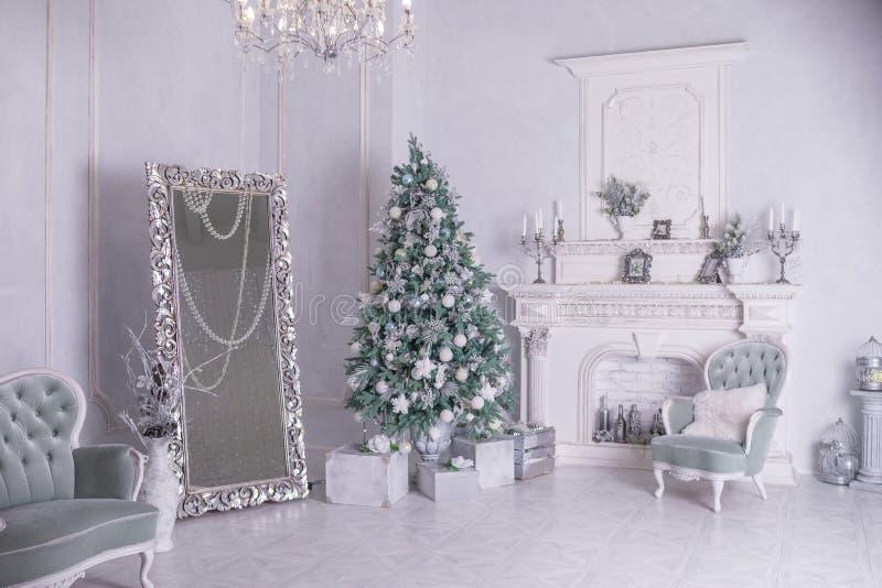 Verzierter Weihnachtsbaum und Geschenkboxen im Wohnzimmer großes weißes Wohnzimmer mit Weinlesemöbeln und einem großen stockbilder