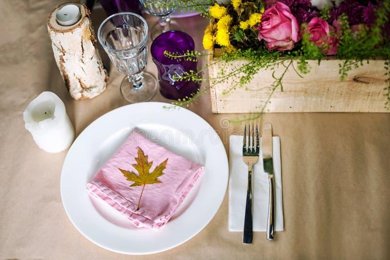 Verziertes tischfertiges für Abendessen Schön verzierte Tabelle stellte mit Blumen, Kerzen, Platten und Servietten für die Heirat stockfoto