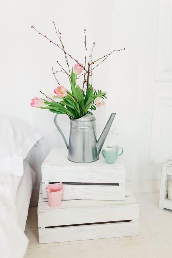 Verzinken Sie Gießkanne mit rosa Tulpen über weißem Hintergrund im Schlafzimmer stockfoto
