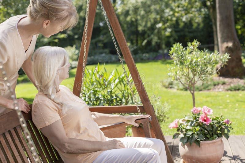 Verzorger die ontspannen hogere vrouw in het terras supporrting tijdens de zomer royalty-vrije stock fotografie