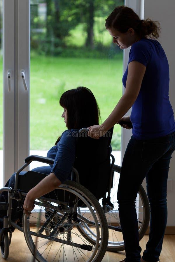 Verzorger duwende rolstoel met gehandicapte vrouw stock afbeelding